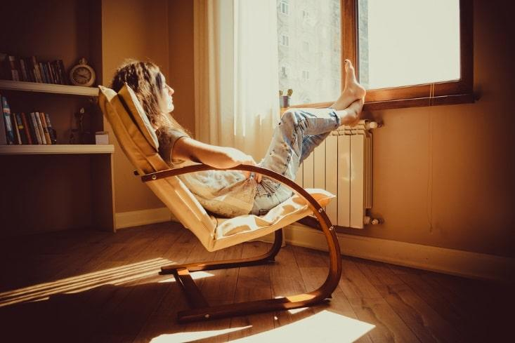 woman relaxing in chair in front of window sunlight barefoot