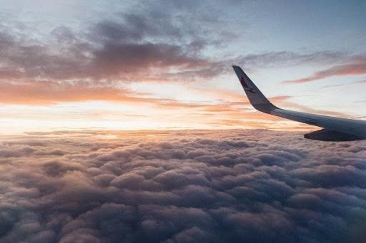 plane flying across sky clouds sunset wing airline