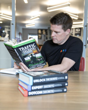 Russell Brunson reading Trilogy Books