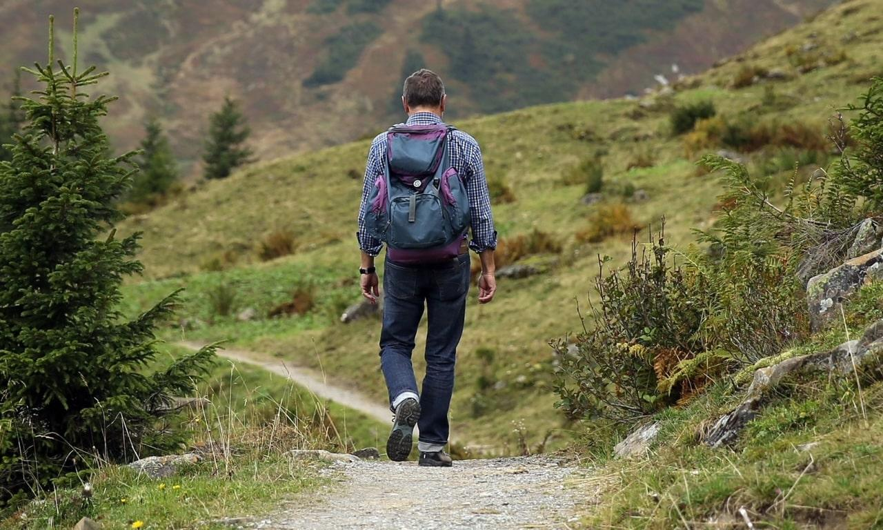 man hiking with backpack through woods